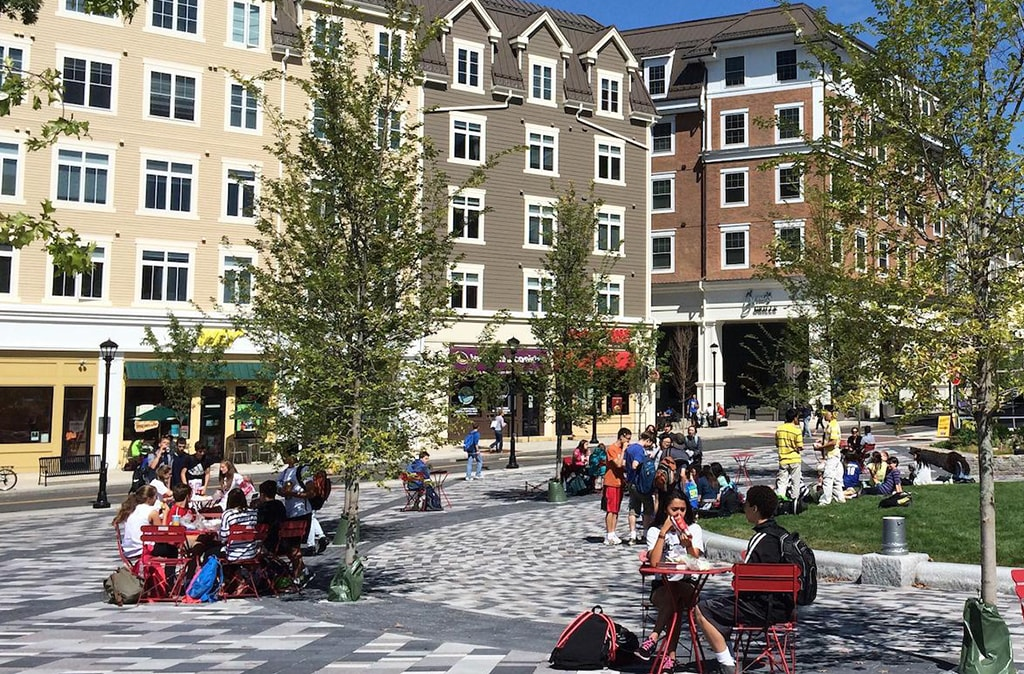 Students sitting at tables enjoying leisure time in busy college courtyard Charter Realty