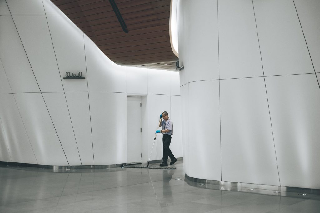 Janitor cleaning floor in upscale modern office building